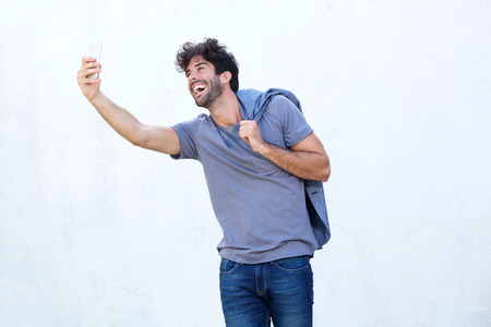 Side portrait of happy man taking selfie with mobile phone Lizenzfreie Bilder