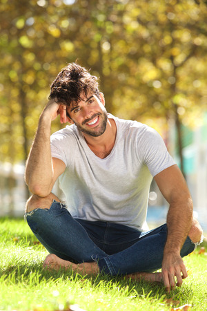 Full body portrait of handsome man sitting outside in grass leaning head on hand