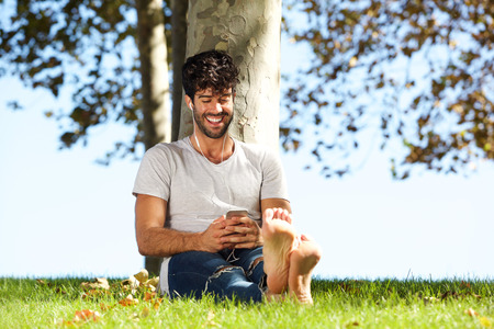Full body portrait of happy man sitting outside with mobile phone and headphones Lizenzfreie Bilder
