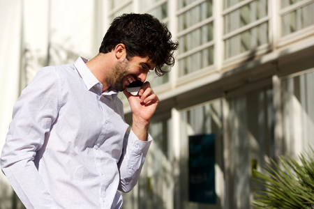 Side portrait of handsome man standing outside talking on smart phone Lizenzfreie Bilder