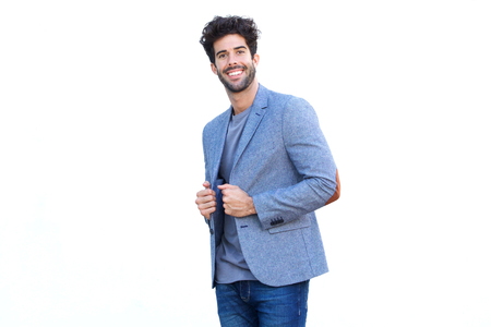 Portrait of handsome man standing in blue blazer smiling by white wall