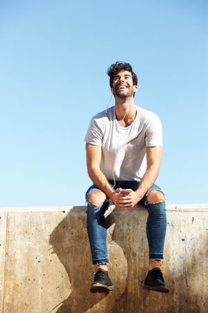Full body portrait of happy man sitting on concrete wall with earphones and cellphone