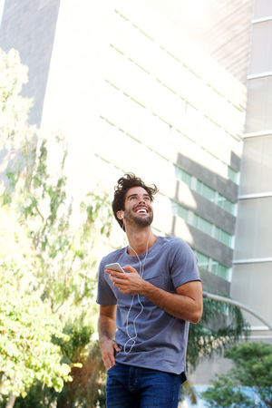 Portrait of laughing man standing on urban street holding smart phone