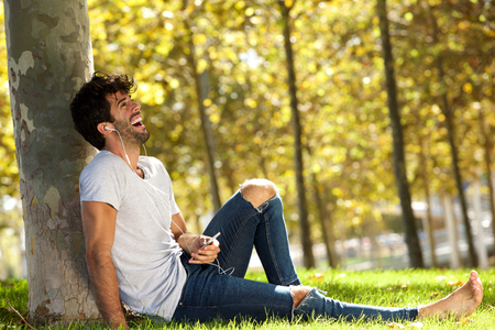 Full body portrait of laughing man sitting in grass with cellphone and headphones Lizenzfreie Bilder