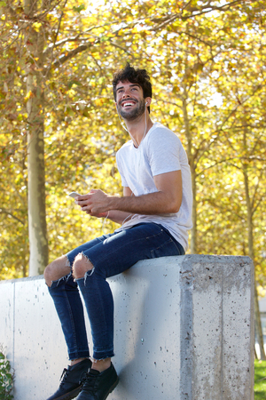 Full body portrait of laughing man sitting by trees with cellphone and headphones