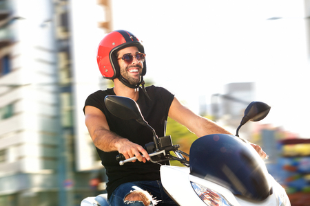 Side portrait of happy man with helmet on motorcycle ride in city