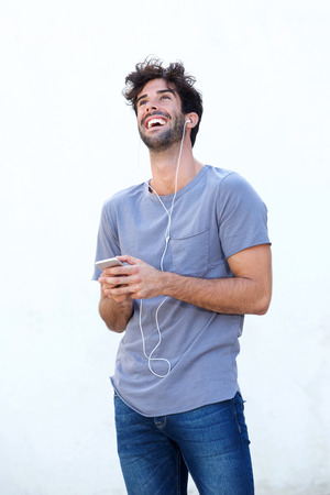 Portrait of carefree man holding mobile phone listening to music