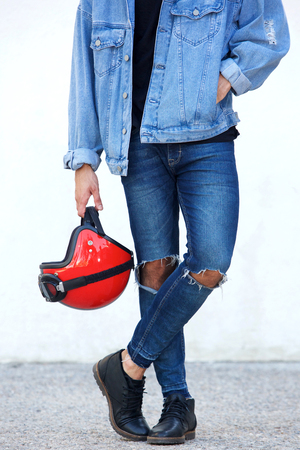 Low portrait of motorcyclist with ripped jeans holding helmet
