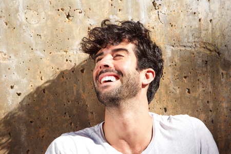 Close up portrait of laughing carefree man sitting by concrete wall