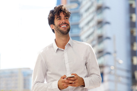 Portrait of happy confident man standing in city with mobile phone