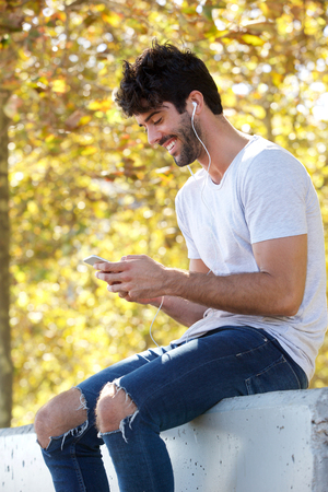 Side portrait of smiling handsome man sitting outside with headphones and mobile phone Lizenzfreie Bilder