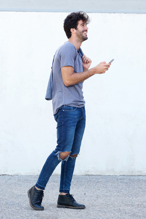Full body side portrait of handsome happy man walking with mobile phone