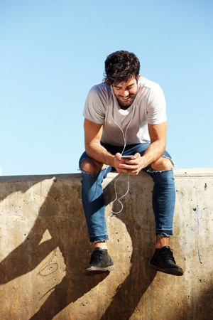 Full body portrait of cheerful man sitting on concrete wall with headphones and cellphone