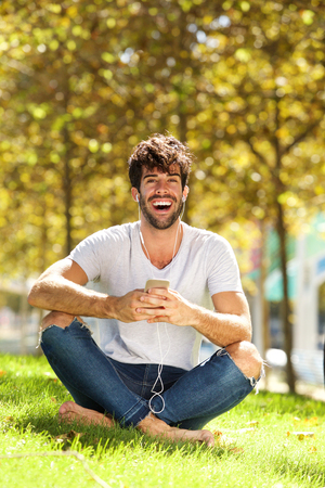 Full body portrait of laughing man sitting in grass listening to music