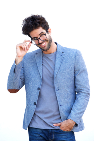 Portrait of handsome man in blue blazer standing with hand on glasses
