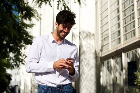 Portrait of happy handsome man standing outside in city holding cellphone