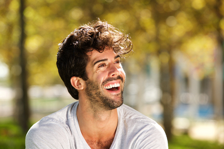 Close up portrait of handsome man with beard laughing outside Lizenzfreie Bilder