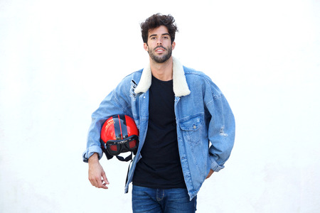 Portrait of serious motorcyclist wearing jean jacket and holding helmet