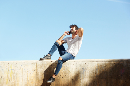 Full body portrait of cheerful man sitting on concrete wall talking on smart phone