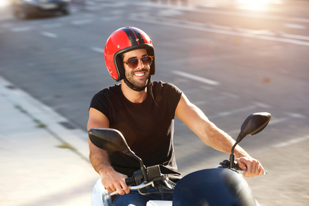 Side portrait of happy man with helmet and sunglasses on motorcycle ride