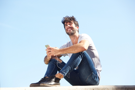Full body portrait of happy man sitting on wall with headphones and cellphone