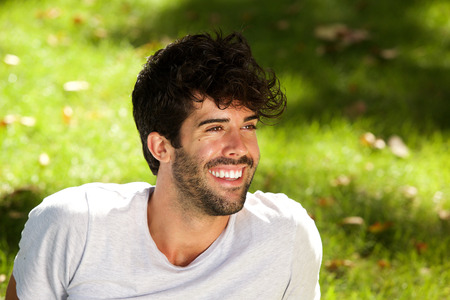Close up portrait of laughing handsome man with beard sitting in grass