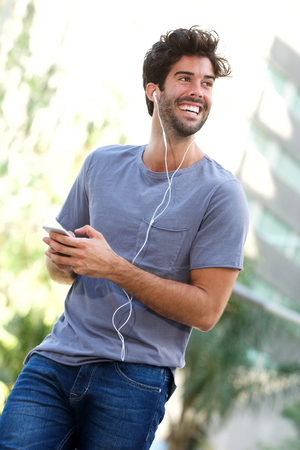 Portrait of smiling man standing in city with headphones and cellphone Lizenzfreie Bilder
