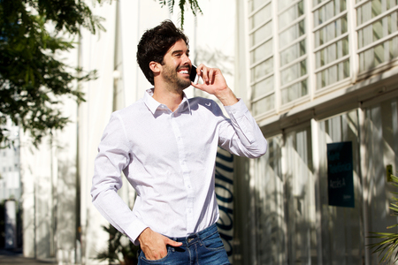 Profile portrait of smiling man standing and talking on phone in city
