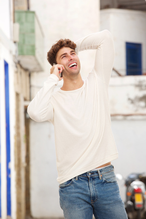 Portrait of young man standing with hand on head talking on mobile phone