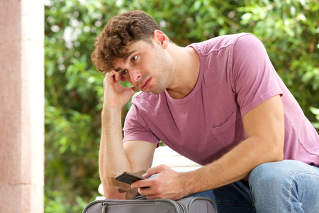 Side portrait of stressed man sitting on park bench with suitcase and cellphone