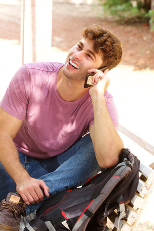 Side portrait of happy man sitting on park bench with backpack and cellphone