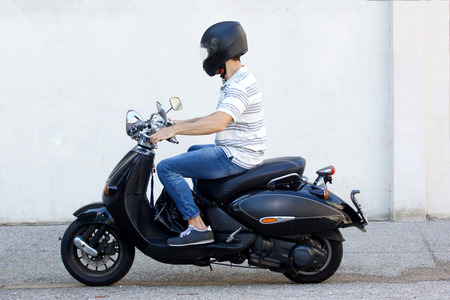 Side view portrait of young man in helmet riding a scooter on road Standard-Bild