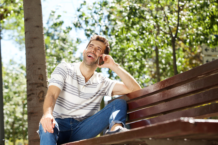 Portrait of laughing young man sitting outdoors on bench and using mobile phone