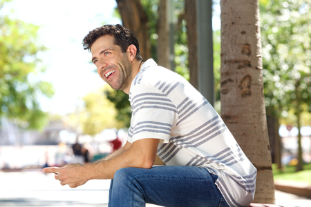 Portrait of handsome young man sitting outdoors with mobile phone and laughing