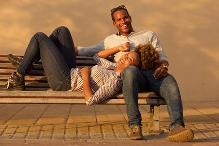Ritratto di belle coppie di risata che si siedono sul banco di parco fuori Archivio Fotografico - 92873021