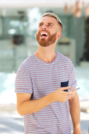 Portrait of young man laughing with cell phone