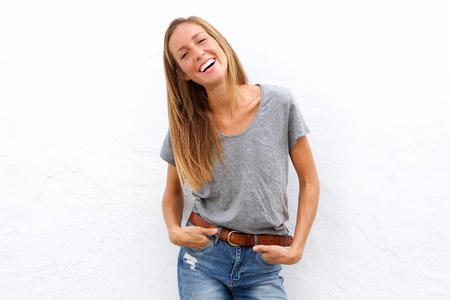 Portrait of a confident young woman laughing against white background Stock fotó