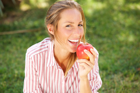 Portrait of attractive young woman eating apple in the park
