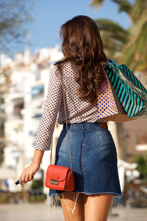 Rear portrait of woman walking in jean skirt with gift bags and cellphone Foto de archivo