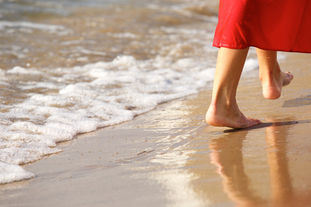 Close up portrait of woman in red walking barefoot on beach by waves