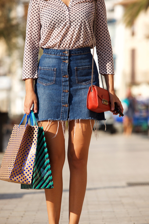 Close up partial portrait of woman with purse holding shopping bags and smart phone Stock Photo