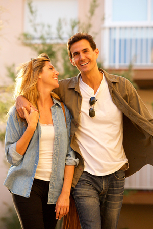 Portrait of happy couple walking together on date laughing