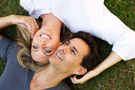 Close up portrait of happy couple lying on grass together in love