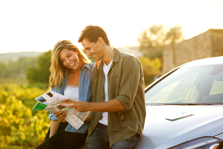 Portrait of couple sitting on car looking at map together
