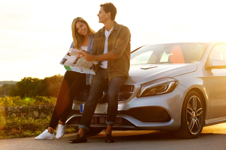 Full length portrait of couple sitting on car lost and looking at map