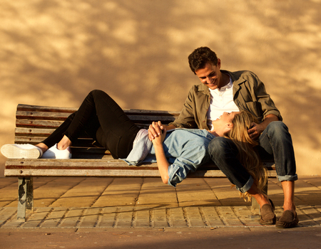Full body portrait of happy woman and man in embrace on park bench