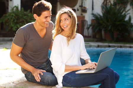 Portrait of couple sitting outside together by pool with laptop