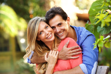 Close up portrait of carefree couple in love sitting outside in embrace Standard-Bild