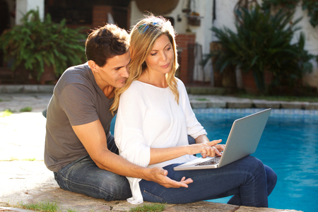 Portrait of couple sitting outside working on laptop together