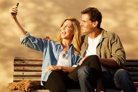Portrait of happy pair sitting outside on park bench taking selfie Standard-Bild